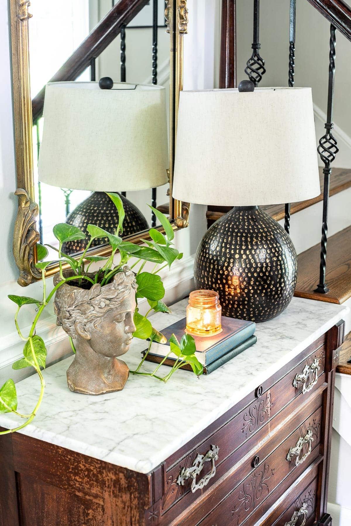 Classic timeless modern foyer - bust planter, table lamp, chest styling vignette