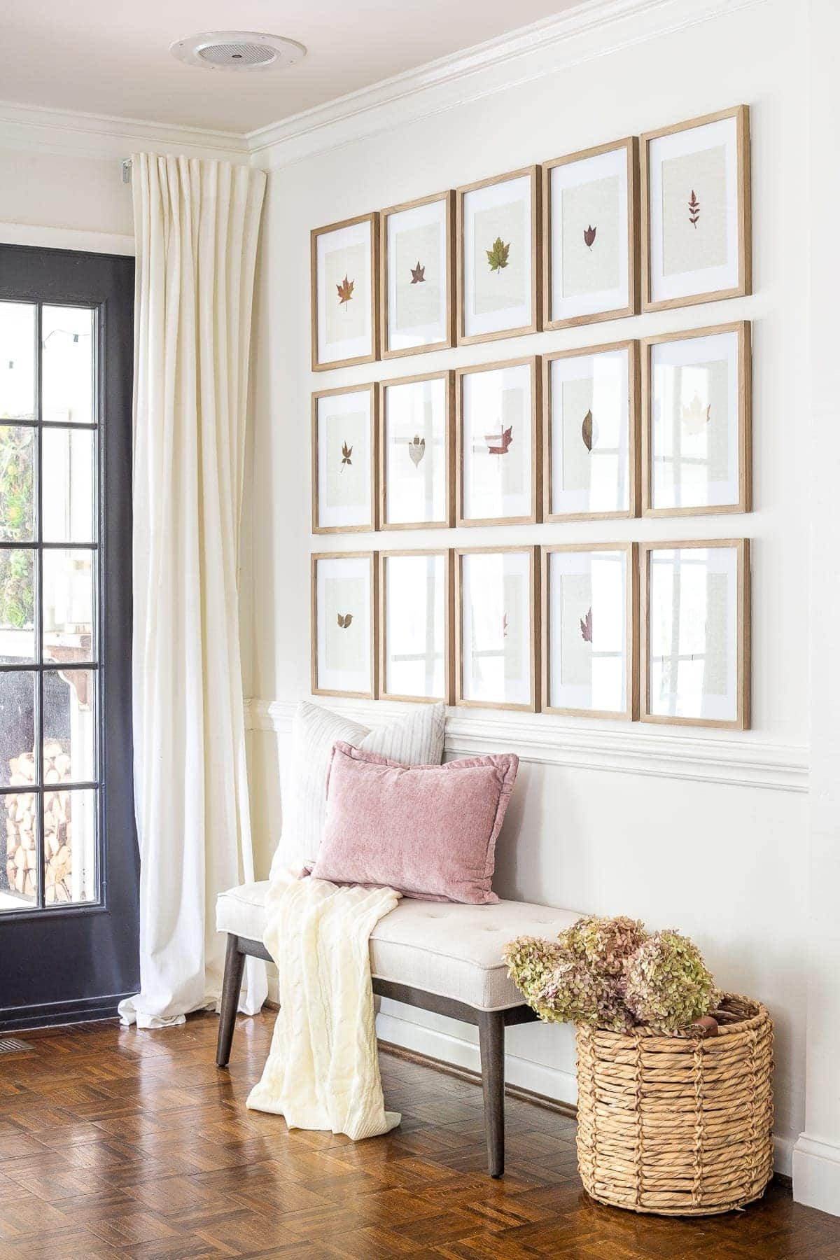 entryway decorated for fall with pressed leaf gallery wall and basket of dried hydrangeas