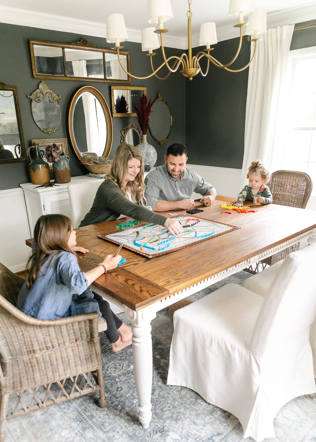 family playing board game at dining room table with gallery wall of mirrors behind