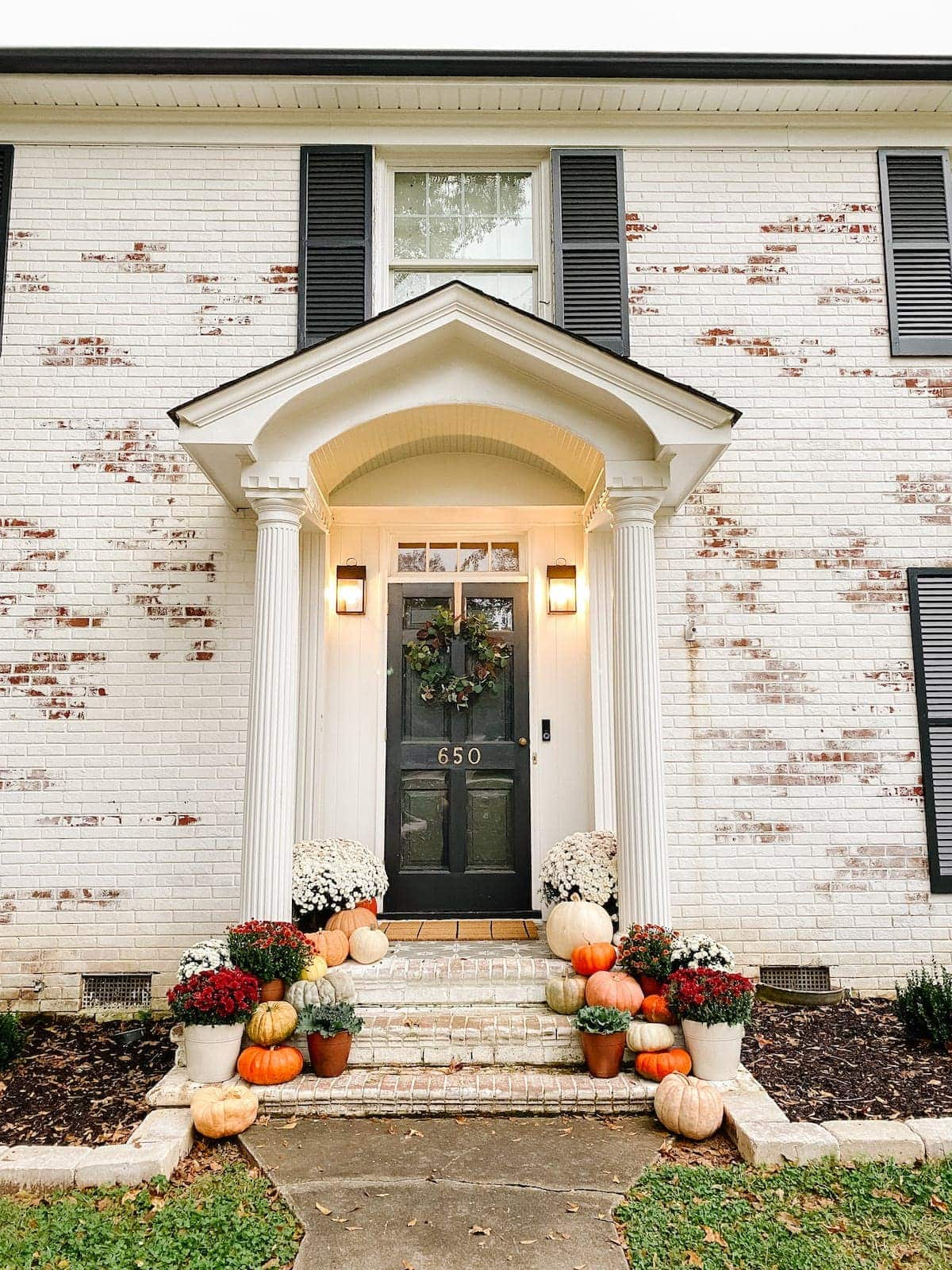 Colorful Fall Porch Stoop Decorated with Mums and Pumpkins with Limewashed Brick