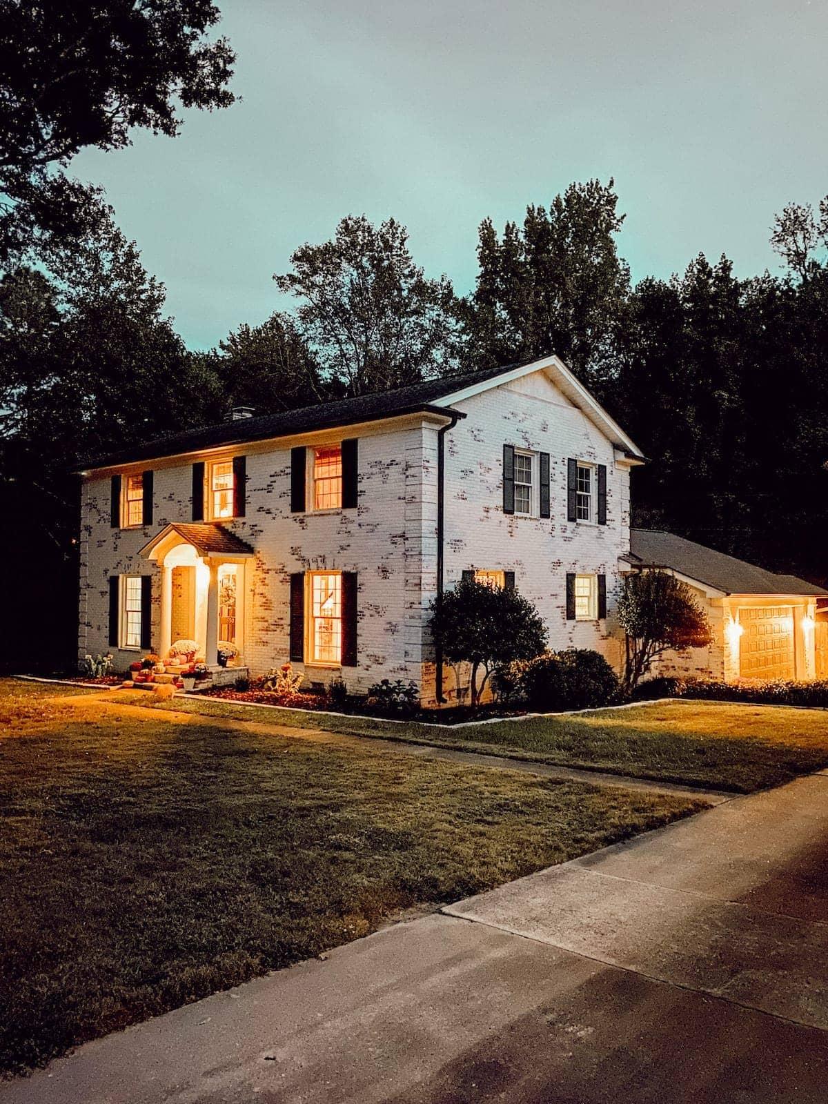 limewashed brick colonial house at night