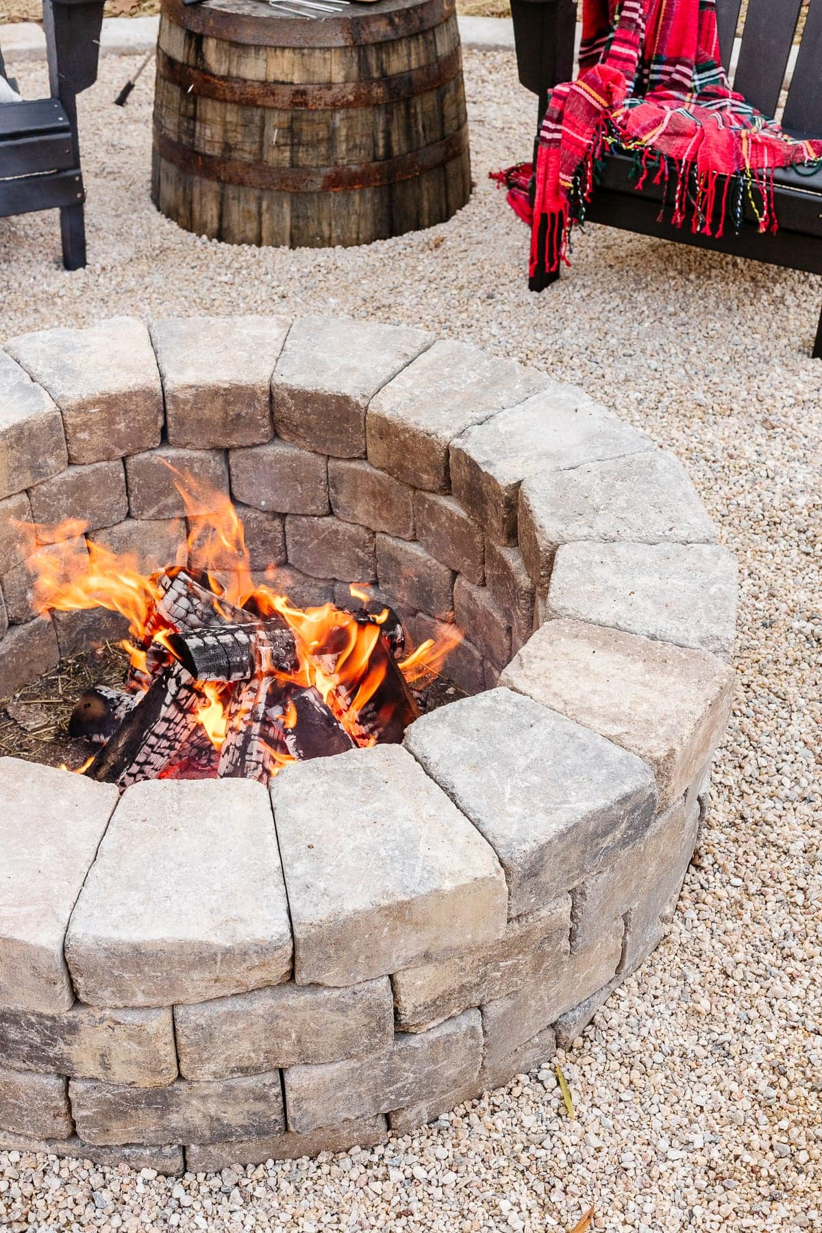 stone fire pit with pea gravel and adirondack chairs