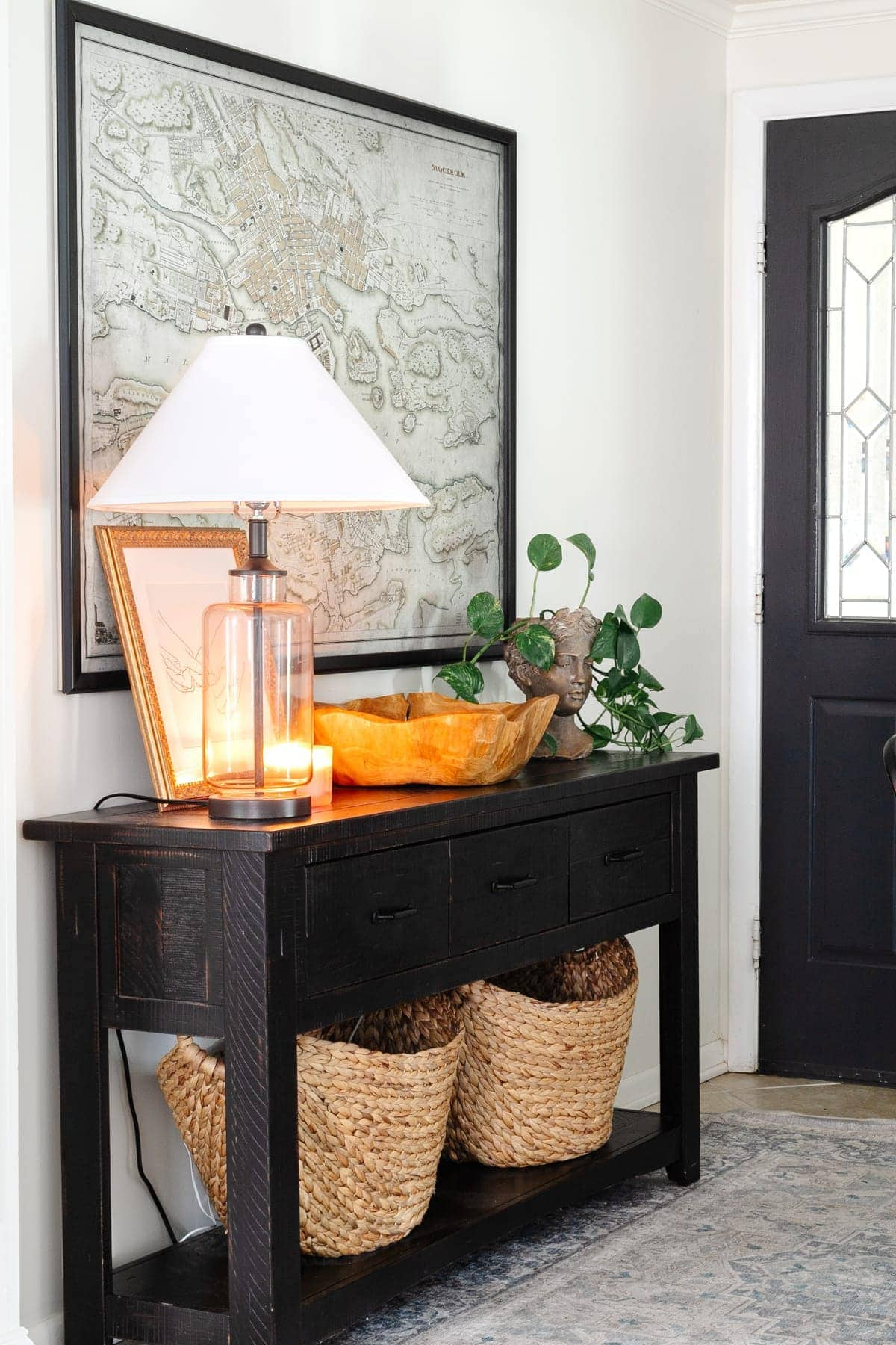 black entryway table with baskets, bust planter, lamp, and map art. White walls and black door