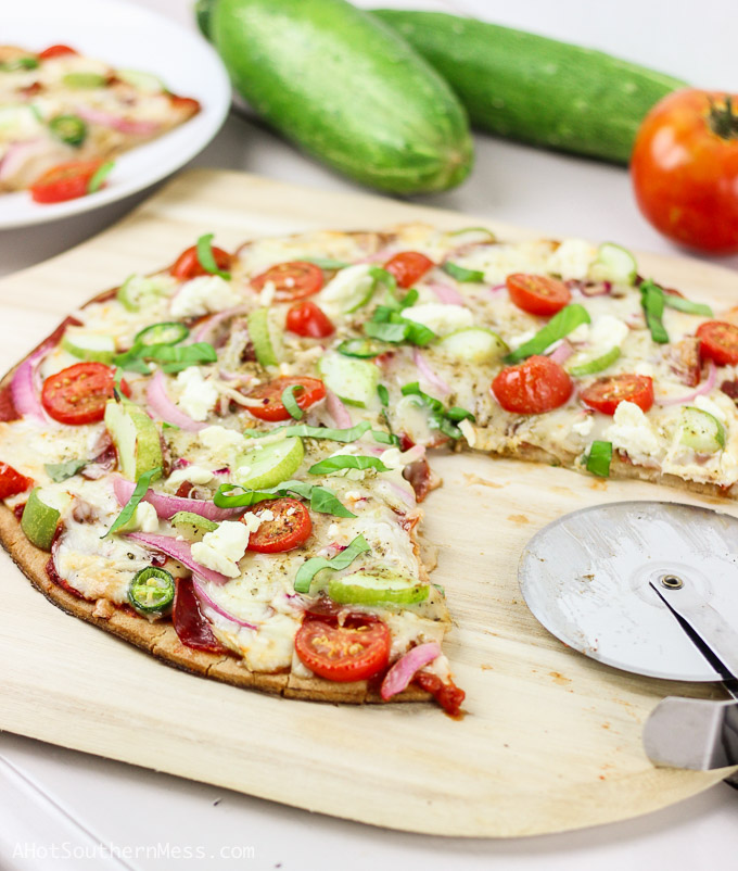 A delicious gluten-free spin on a summer veggie pizza. This Cucumber Salad Pizza is piled high with fresh crisp cucumbers, sweet sliced cherry tomatoes, brisk bites of jalapeño, slices of red onion, and sprinkled with fresh feta cheese crumbles. Everything you'd find in a cucumber salad, now tops your dang pizza y'all! {throws up her hands in mind-blowing fashion} www.ahotsouthernmess.com