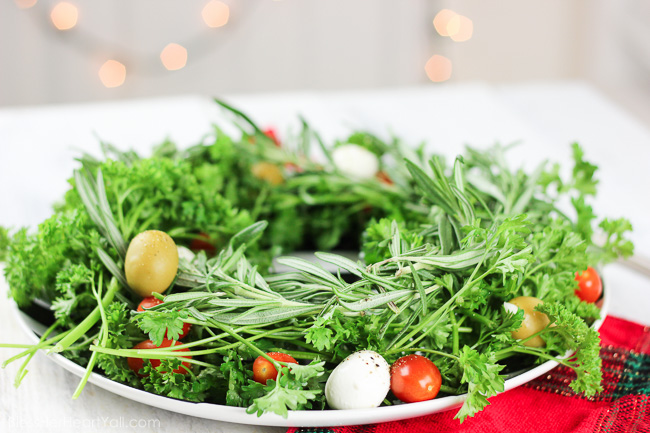 This holiday olive wreath is a festive holiday appetizer that is not only easy to put together, put easily adaptable to the party-goers likes and needs. Plate your favorite herbs underneath tasty mozzarella cheese, sweet tomatoes, and your favorite olives. Sprinkle cracked pepper and a delicious balsamic drizzle to finish! www.blessherheartyall.com