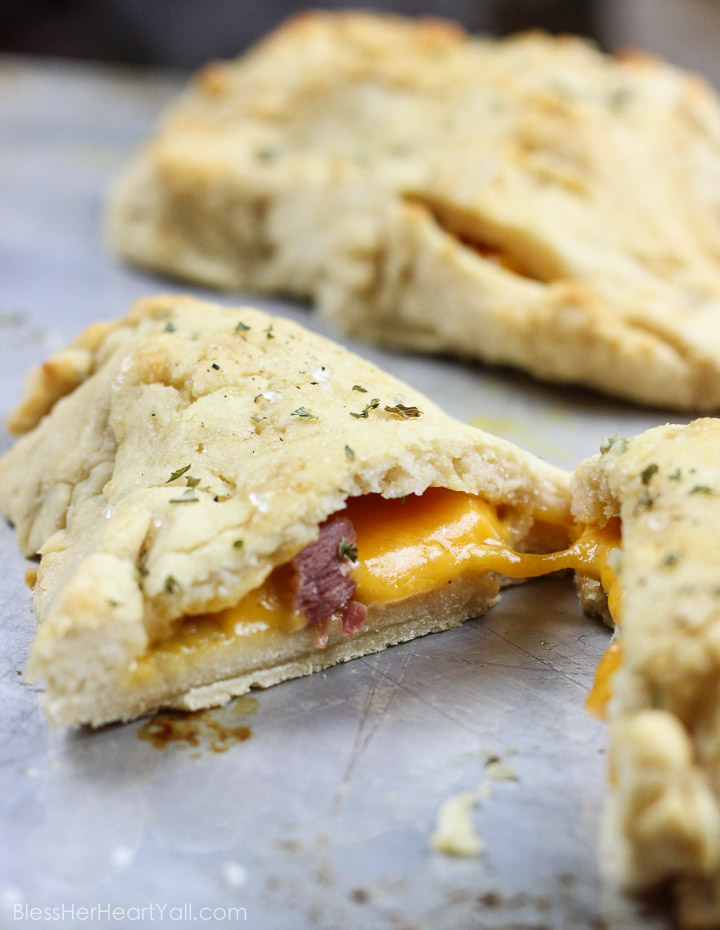 These gluten-free ham and cheese hot pockets are the real deal! Perfectly crispy pockets of smooth soft dough are stuffed with leftover Christmas ham and melty cheese, closed up, and brushed with an olive oil, honey, brown sugar, and garlic sauce. It's the perfect tasty meal on-the-go and a great way to finish off those Christmas ham leftovers! www.blessherheartyall.com
