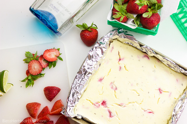 These gluten-free strawberry basil margarita cheesecake squares are the ultimate refreshingly sweet party carb. With hints of lime and a splash of tequila, along with fresh chopped basil and strawberries, these cheesecake bites will blow your mind with every sweet and zesty bite!