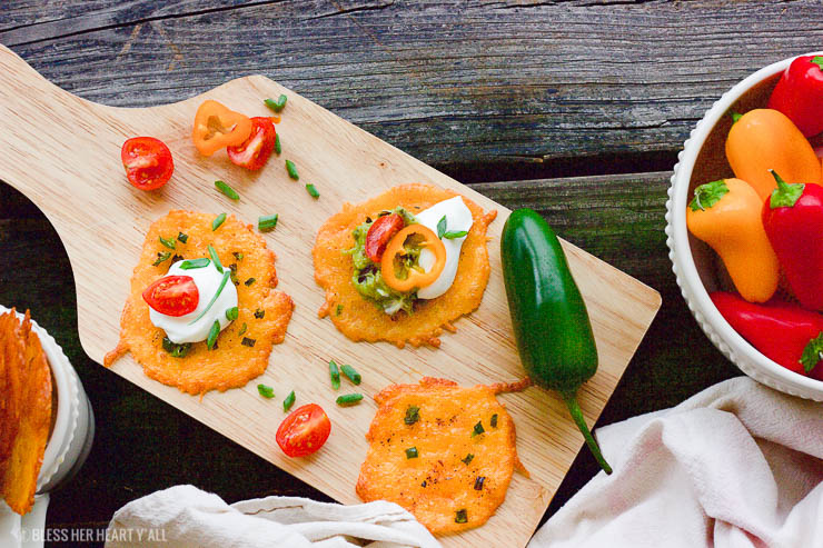 Taco cheese crisps are an easy and quick baked party recipe! These crispy cheese dippers are the perfect appetizer or snack for any gluten-free or low carb munchers and are huge hits at tailgating parties! All you need is cheddar cheese, taco seasoning, your favorite taco toppings, and a few minutes of oven time! Yes!