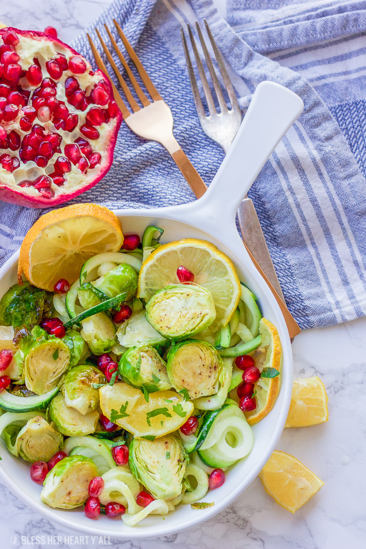 This lemon garlic roasted brussel sprouts + zucchini recipe is a clean, crisp, savory vegetable dish that is not only healthy but a gorgeous and easy addition to any meal! Lemon, honey, and garlic flavors coat the roasted brussel sprouts, zucchini noodles, and pomegranate arils for a colorful fresh salad.