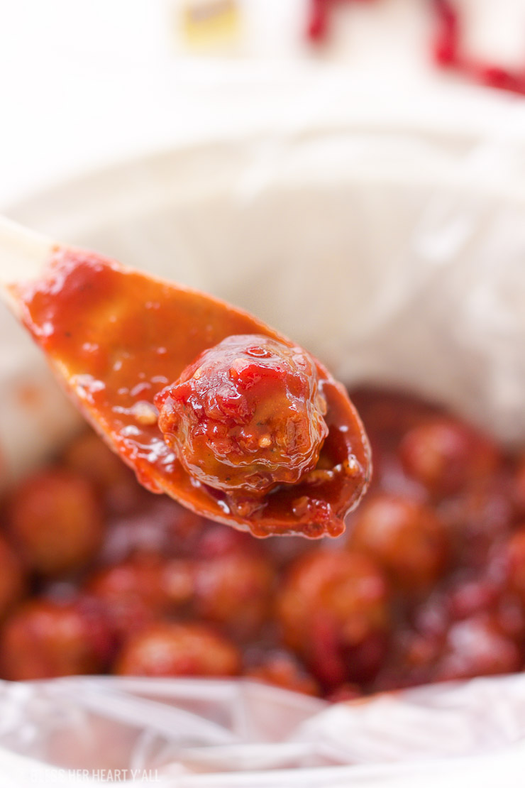 These spicy cranberry bacon bbq meatballs are the ultimate in sticky finger foods just in time for the holidays! A quick homemade cranberry sauce is melted and smothered into barbecue sauce and hot spices for the perfect sweet and spicy no-fuss pop-able party bites!