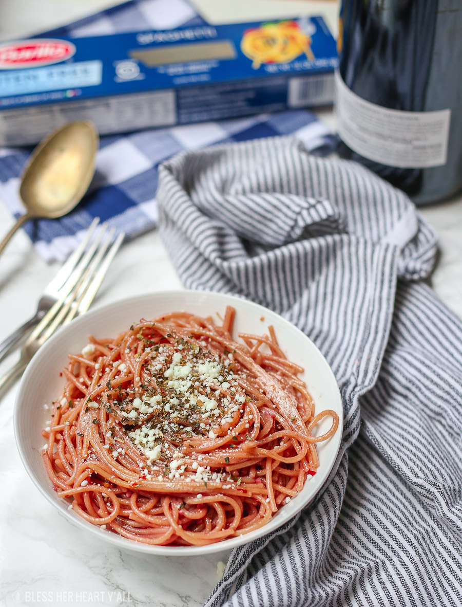 This gluten free red wine pasta + garlic basil goat cheese sauce is the perfect quick and fancy date night recipe that's ready in under 20 minutes! The gluten free pasta is cooked and stained in red wine and then tossed in a creamy garlic basil goat cheese sauce.