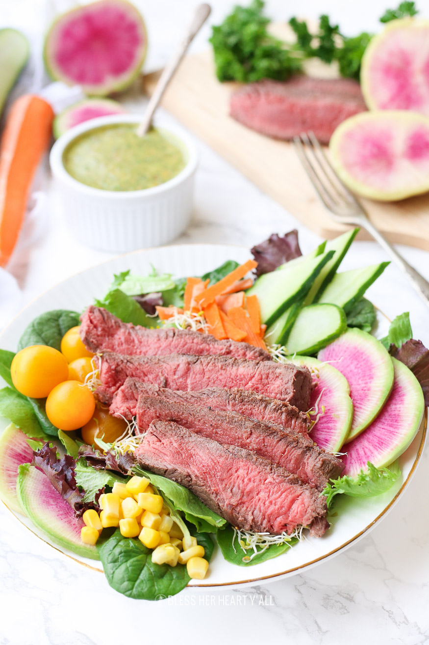 This spring steak salad with homemade carrot and cilantro chimichurri vinaigrette dressing uses crisp spring vegetables and tops them with tender juicy steak pieces and a drizzle of fresh herb chimichurri sauce. Colorful vibrant vegetables combined with high-quality steak choices from our sponsor PRE Brands make this salad a standout showstopper.