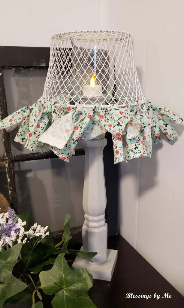 Put the tea light candle in the candle holder and turn the basket upside down over the candle holder