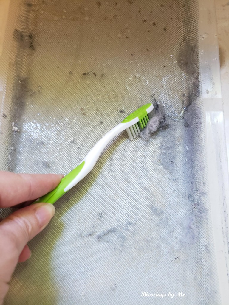 cleaning the lint trap with a toothbrush