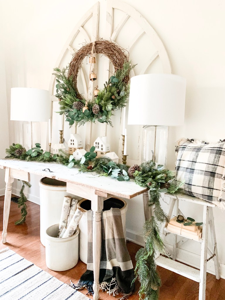 entryway table with large Christmas wreath hanging above it.
