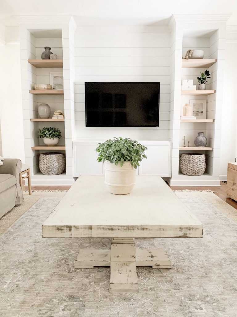 view of living room with shiplapped media built ins