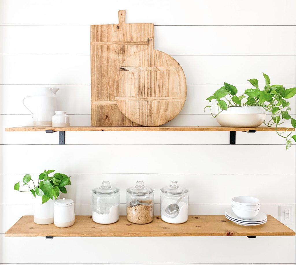 kitchen shelves with plants, jars, and cutting board decor