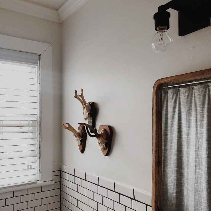 vintage inspired bathroom with antique mirror, mounted animal horns, subway tile and white faux wood blinds covering window