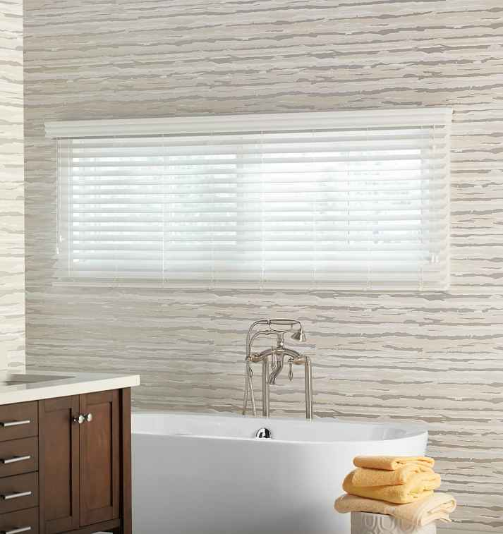 wide window over bathtub covered with white faux wood blinds