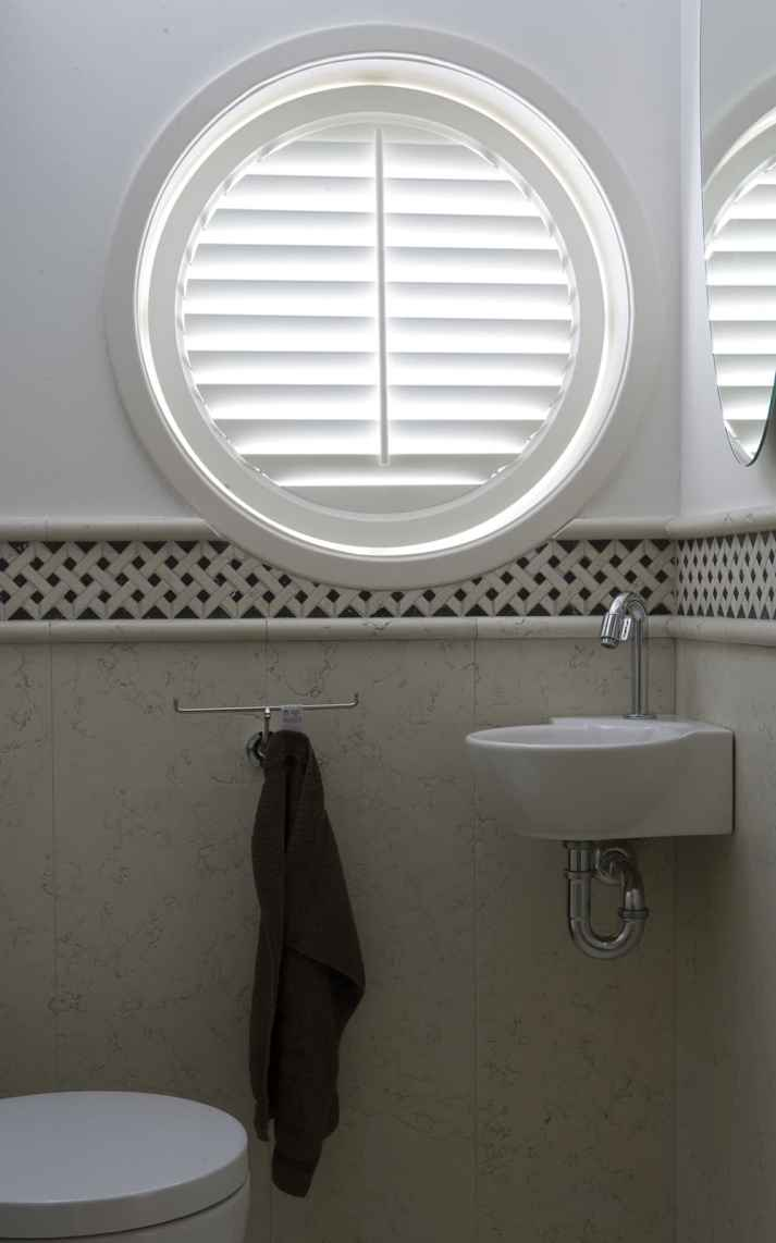 circle window in bathroom covered with custom plantation shutters