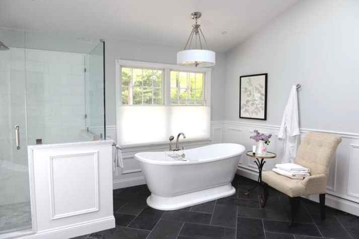 traditional bathroom with freestanding tub and white cellular shades on window with top down option