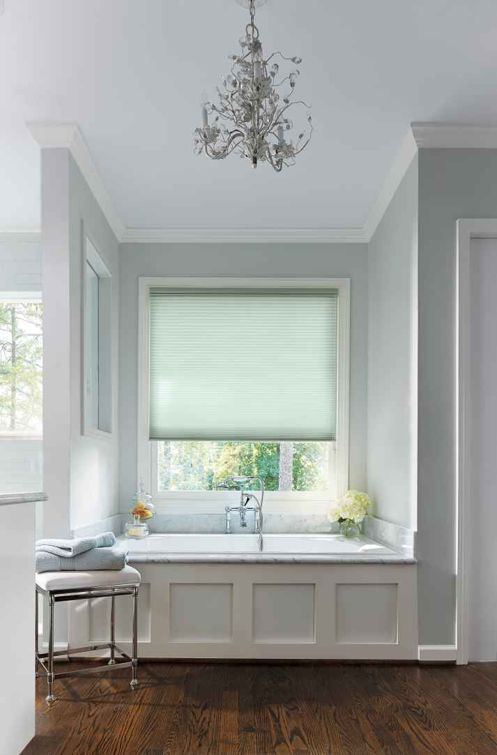 window over built in marble bathtub covered with light blue cellular shades