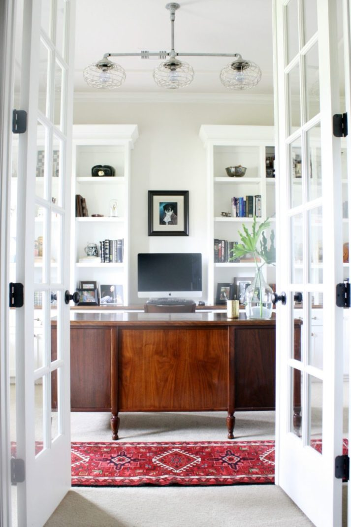 french doors opening into home office with dark wood desk and built in bookcases