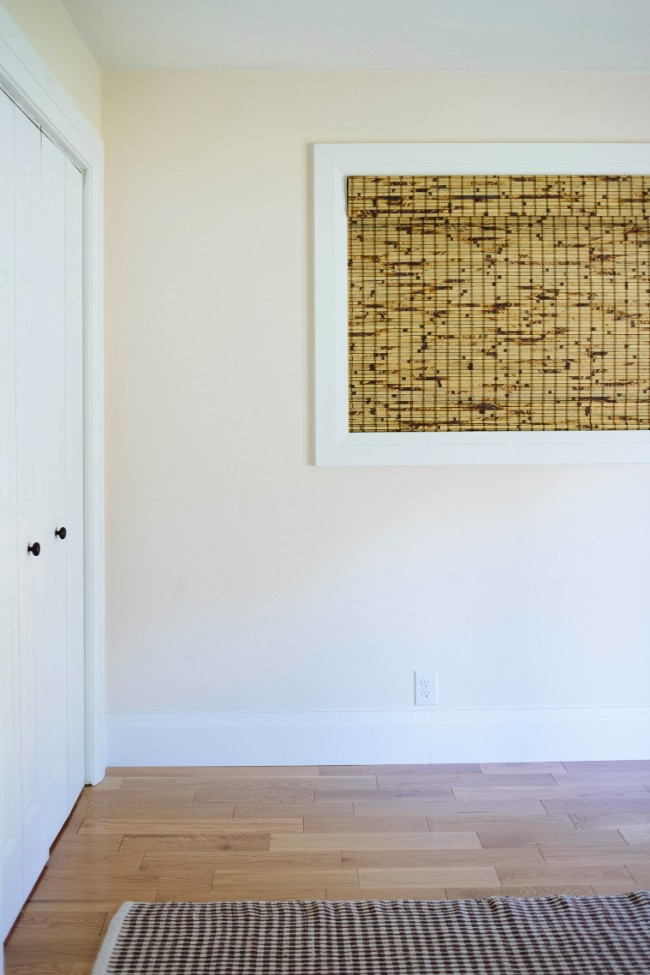 Close-up shot of wide window halfway up wall with bamboo shade
