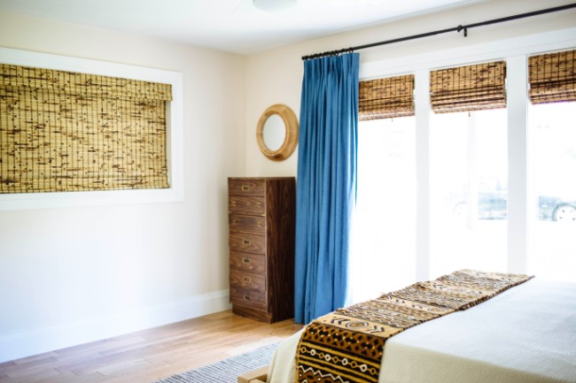 guest bedroom reveal shot with bamboo window shades on short wide window and three smaller windows with blue pinch pleat curtains