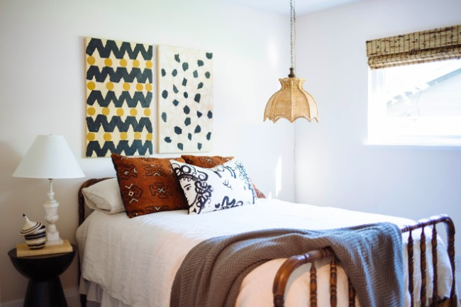 Second guest bedroom reveal shot with African inspired throw pillows on bed, block printed art above headboard, hanging wicker light and woven wood shades on wide window