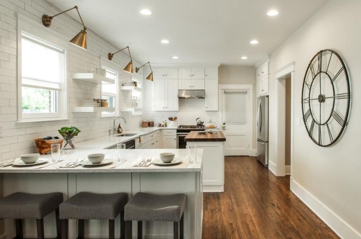 White farmhouse kitchen with 3 windows with white roller shades and natural light pouring in