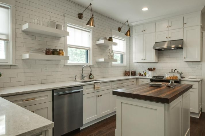 White kitchen with subway tile, white countertops and butcher block island.