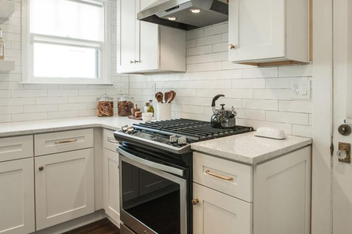 Kitchen with white shaker style cabinets with brass pulls and gas range with vent hood