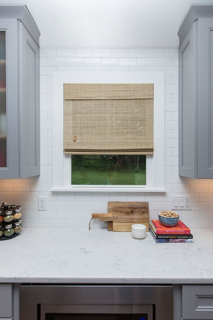 Kitchen with grey cabinets surrounding window with woven wood shades