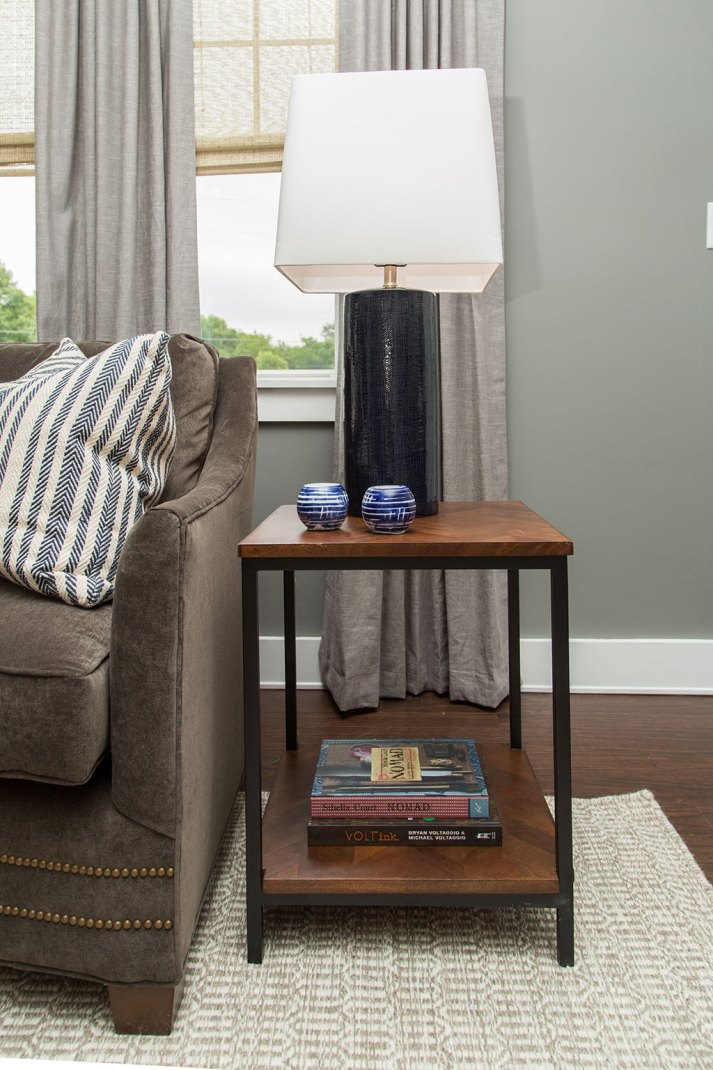 Living room detail shot with industrial wood and metal end table and window with grey curtains and woven grass window shades