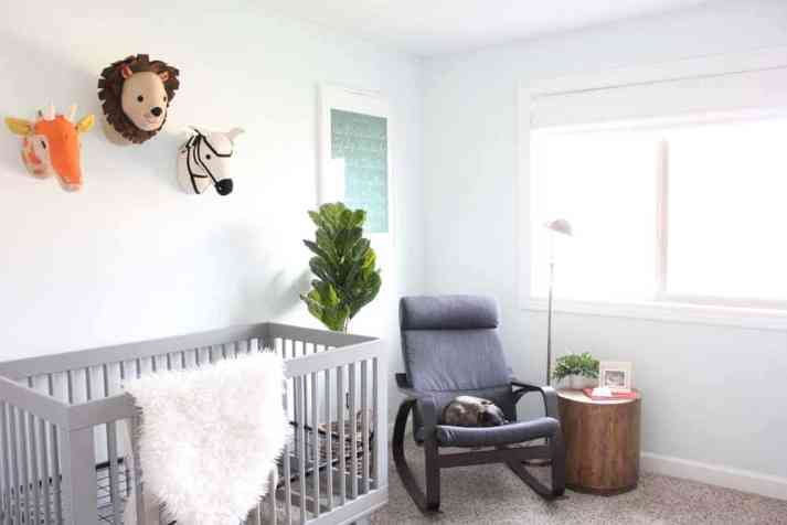 modern nursery with colorful felt animal heads, grey crib, fiddle-leaf fig and white roman shade on window