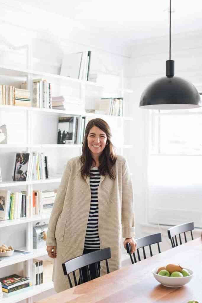 Amanda Jane Jones standing in newly remodeled dining room with open shelving bookcases