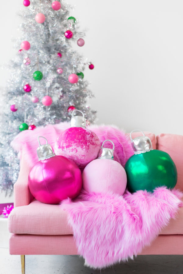 Colorful christmas decor with silver christmas tree, pink and green ornaments and pink couch with DIY ornament pillows