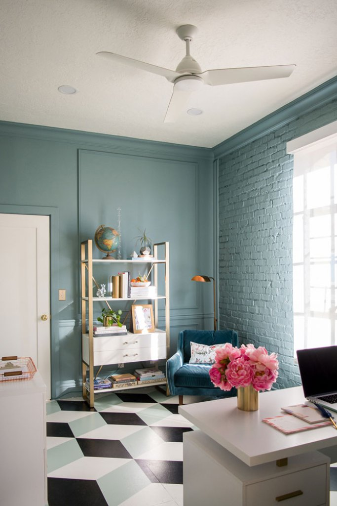 office with wood molding and brick walls painted blue, gold and white modern bookcase and geometric painted floors