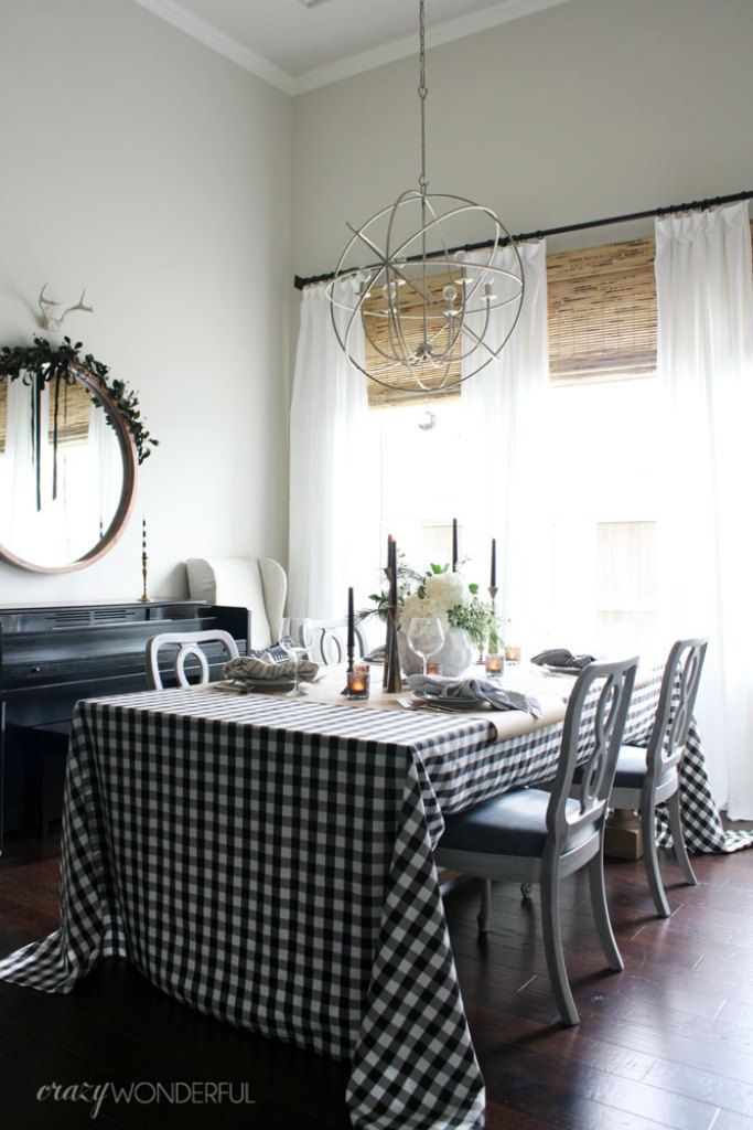 Dining room decorated for Christmas with buffalo check tablecloth and windows with woven wood shades