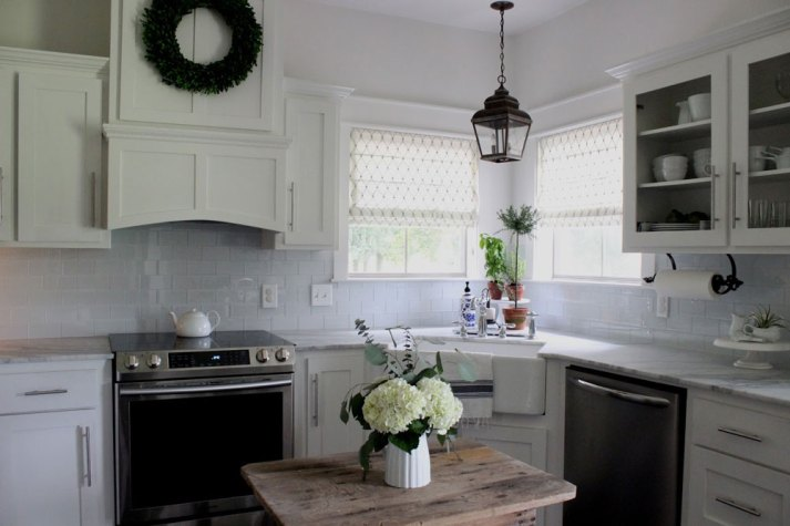 White kitchen with corner farmhouse sink and two windows with printed roman shades