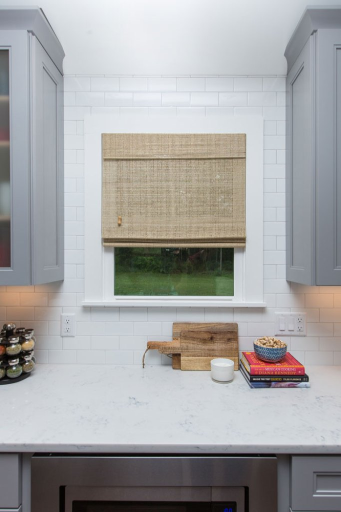 kitchen window with light brown woven window shade and grey cabinets on either side