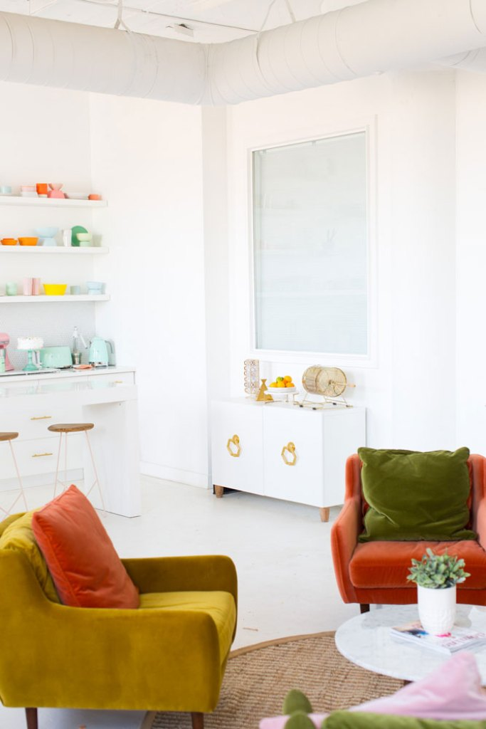 Colorful office with velvet chair sitting area and kitchen with open shelving and brightly colored bowls
