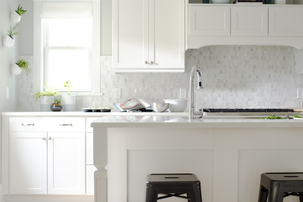 White Kitchen With Small Marble Tile Backsplash And White Roman Shades