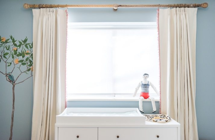 window over changing table with sheer white roller shades and cream pinch pleat curtains with red fringe trim