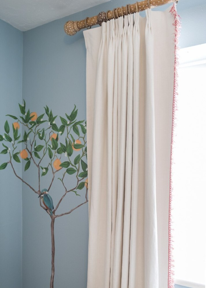 closeup of nursery window with fruit tree and bird mural, white linen curtains with blackout lining