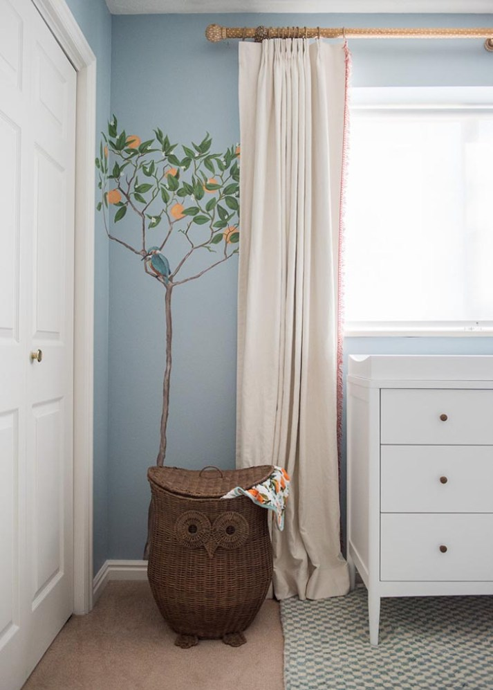 Corner of baby boy nursery with rattan owl hamper, painted orange tree wall mural and cream blackout curtains