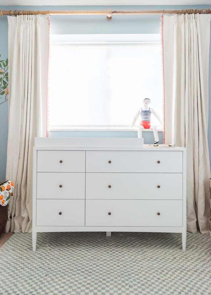 Nursery with blue and white checkerboard rug and white changing table under window with white roller shades and cream pleated curtains with red fringe.