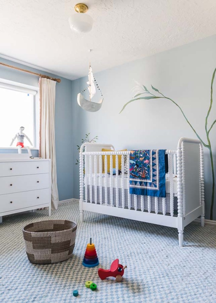 Whimsical nursery with turned wood crib, blue and white checkerboard rug, cream blackout curtains and toys strewn on floor