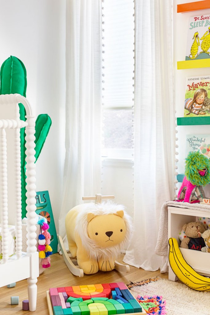colorful gender neutral nursery with white pop pom curtains and cordless white cellular shades
